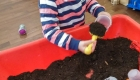 cute baby girl playing with soil